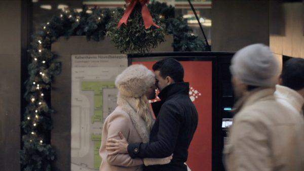 mand og kvinde kysser under en mistelten foran en Coca Cola automat på Hovedbanebården i København
