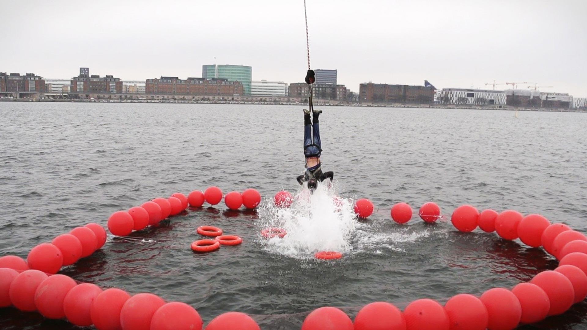 Person kommer op af vandet igen, i et igangværende bungee-jump og er omringet af røde kugler i vandet