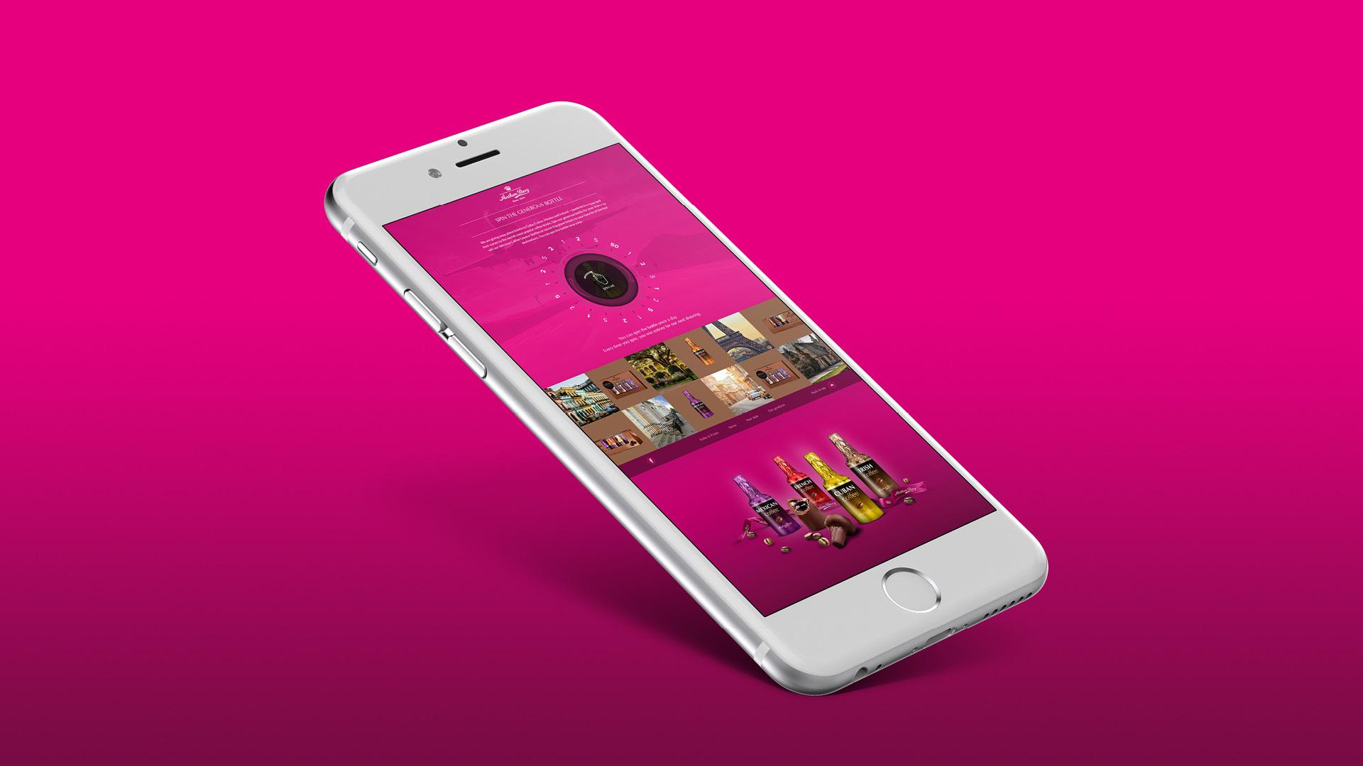 billede af iPhone med screenshot af Anthon Berg Spin the bottle app på lyserød baggrund