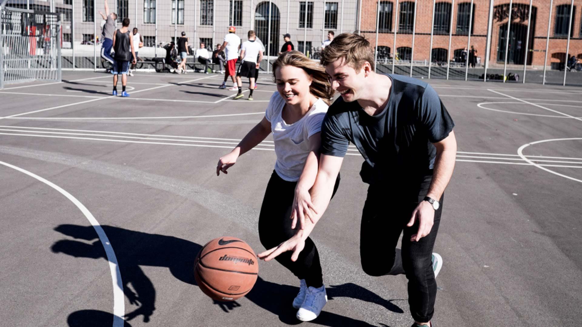 2 unge mennesker spiller basket på Israels Plads