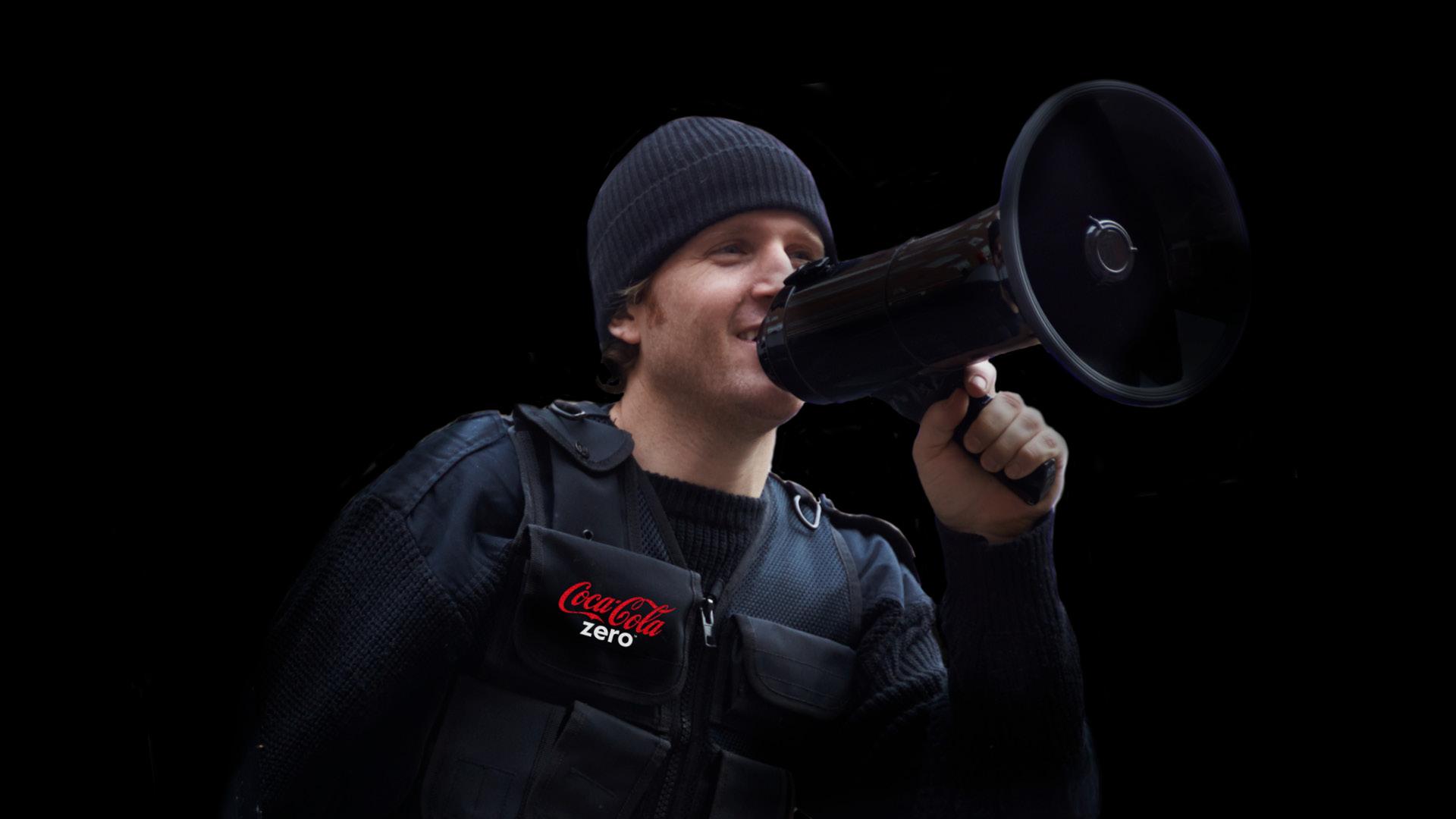 smilende mand med megafon iført en sort Coca Cola vest og hue, på sort baggrund