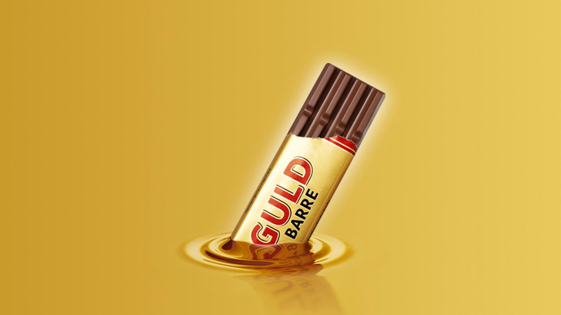 Toms Guldbarre halvt åben og halvt nedsunket i flydende guld på guldbaggrund