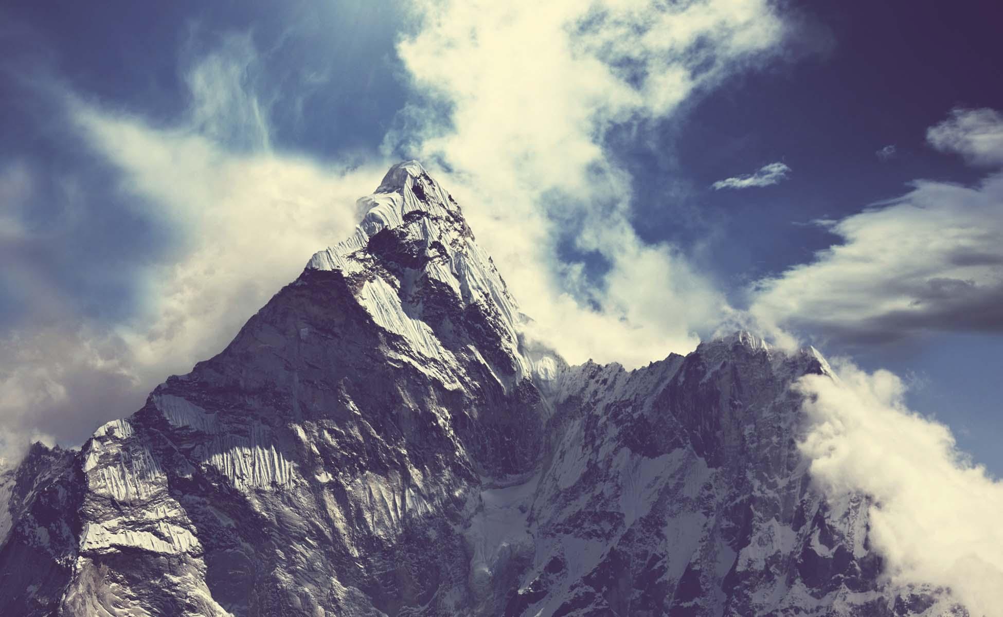 bjerglandskab omringet af skyer og blå himmel