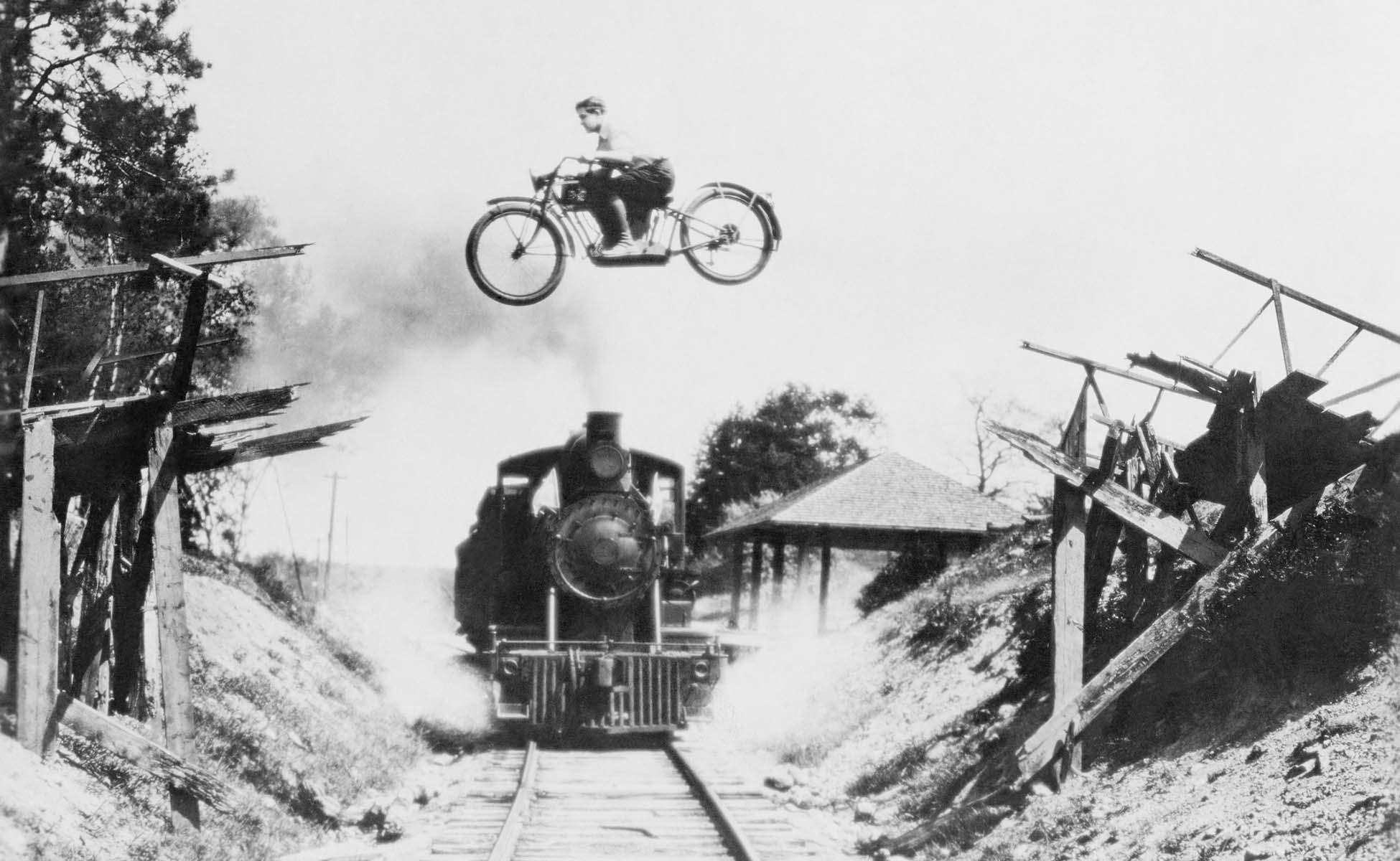 sort hvid billede af ung mand på motorcykel der flyver over en ødelagt bro mens et godstog kører under på skinnerne