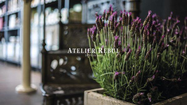 blomsterbed i trækasse med Atelier Rebul logo i front og sløret billede af butikken i baggrunden