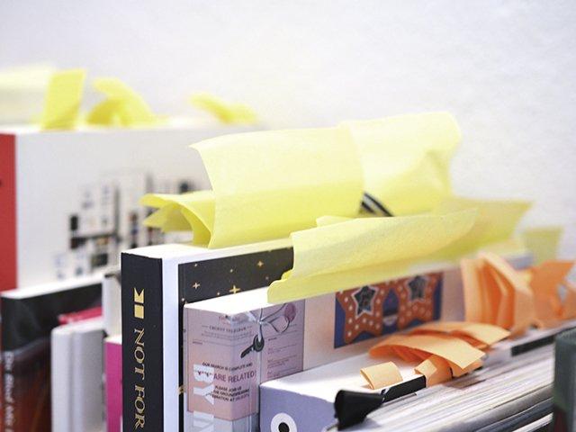 Stående bøger med en masse post stickers og labels.