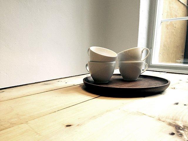 Fire kopper på en mørk træbakke, som står på et lyst træbord.