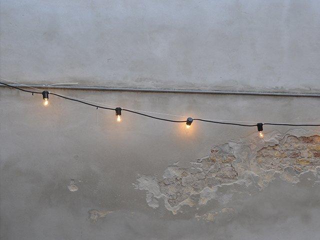 Et krakeleret murværk og en hængende lyskæde.
