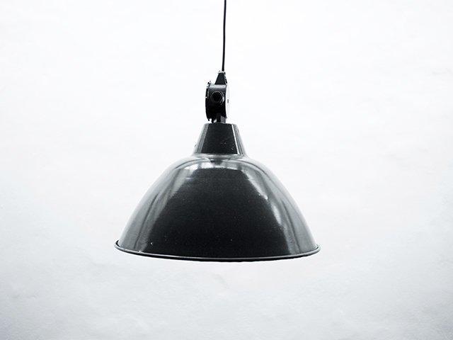 En sort metal pendellampe som hænder foran en hvid væg.